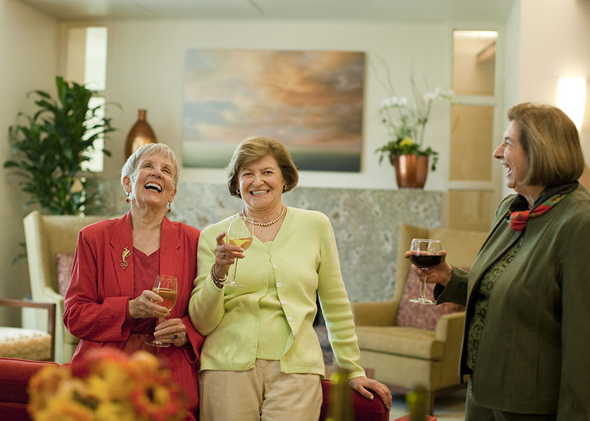 Three women at Moldaw Residences share laughter and a glass of wine